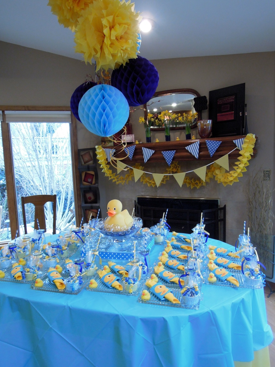 tissue pom poms and honeycomb spheres hung above the table a flag